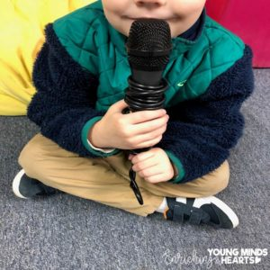 A picture of a student holding a microphone as he is sharing with the class